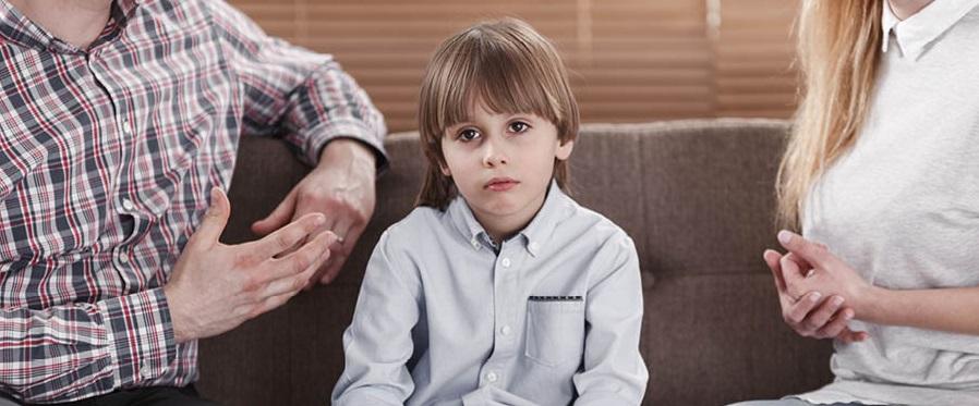 Kind sitzt in der Mitte von streitenden Eltern
