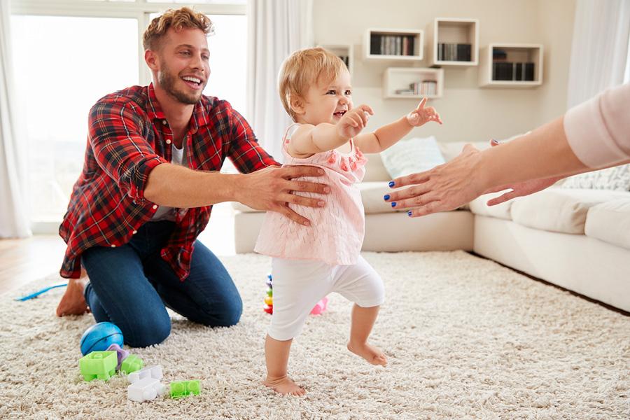Eltern unterstützen Baby beim Laufen lernen