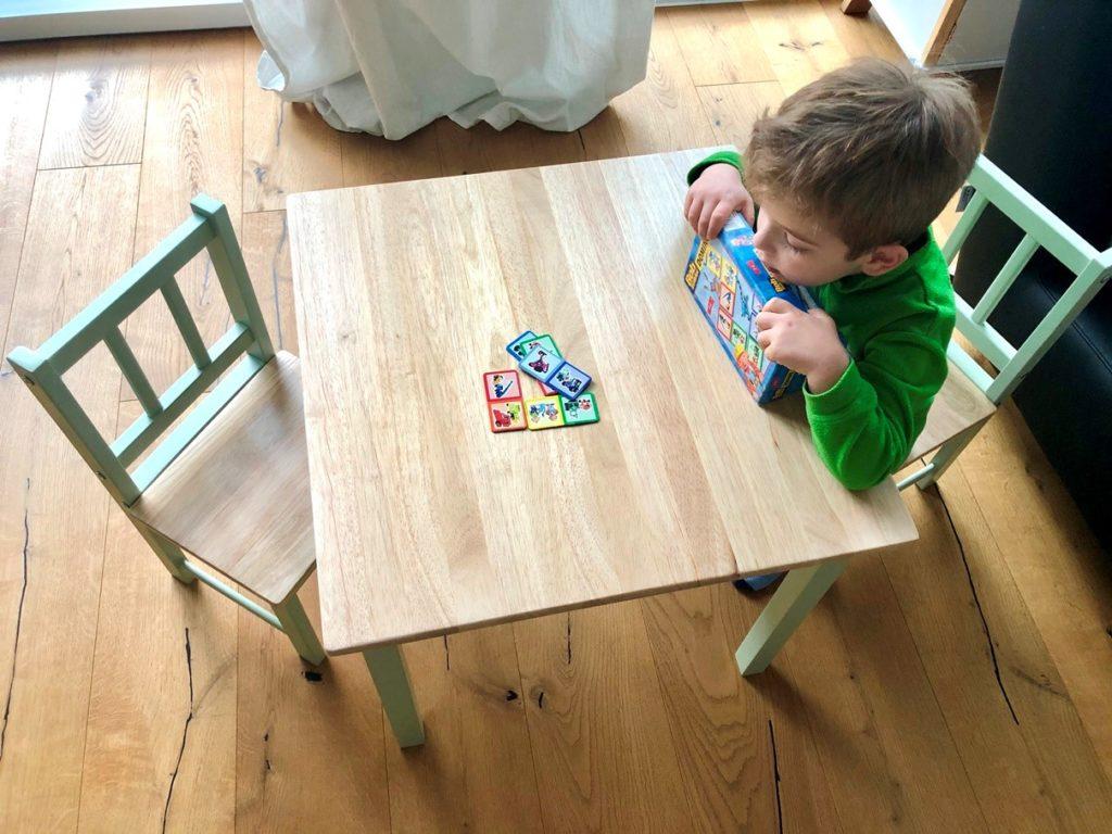 Junge spielt an Kindersitzgruppe mit einem Tisch und zwei Stühlen