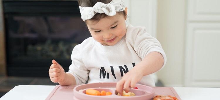 Kleinkind isst von ezpz™ Happy Mat Essmatte rosa rutschfest
