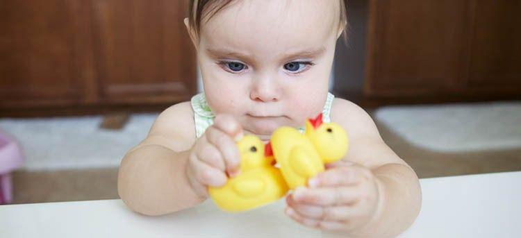 Baby Mädchen schielt auf Spielzeug