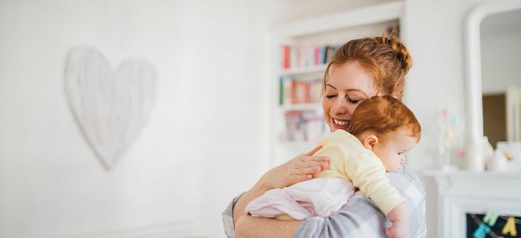 Frau trägt Baby auf dem Arm