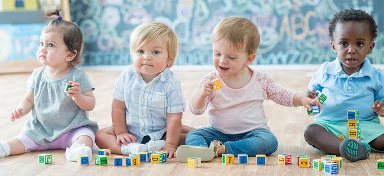Babys sitzen auf dem Boden und spielen