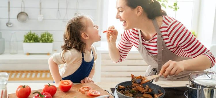 Mutter gibt Tochter ein Stück Gemüse in dem Mund