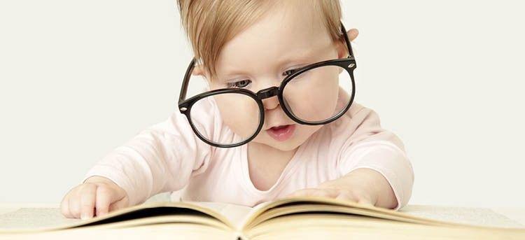 Baby liest Buch mit Brille