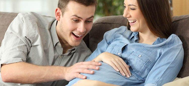 Vater spürt Kindsbewegung auf dem Bauch der Mutter